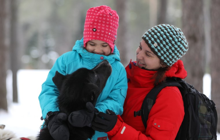 A young girl and her mother interacting with a black sled dog